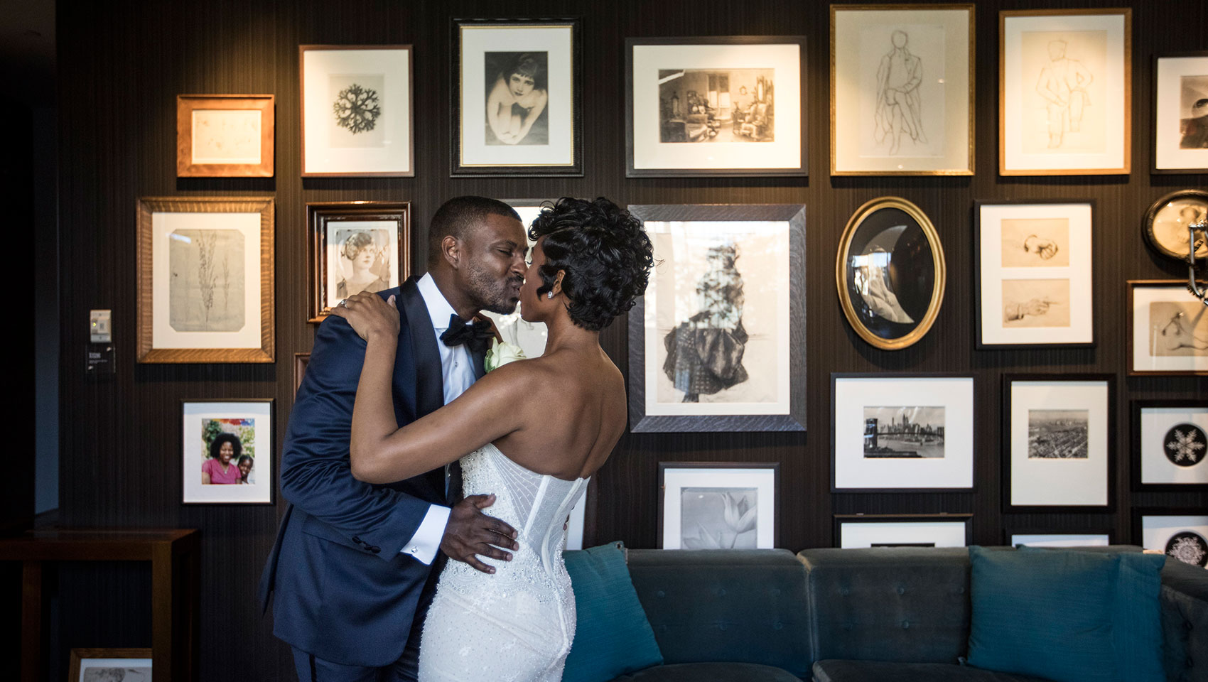 Bride and groom kissing in front of wooden wall with framed pictures and portraits