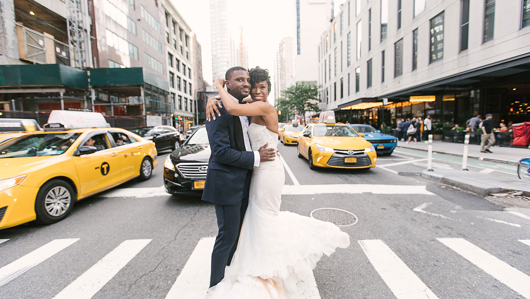 Daniel and Ahkilah embracing each other on a busy crosswalk in front of Kimpton Hotel Eventi