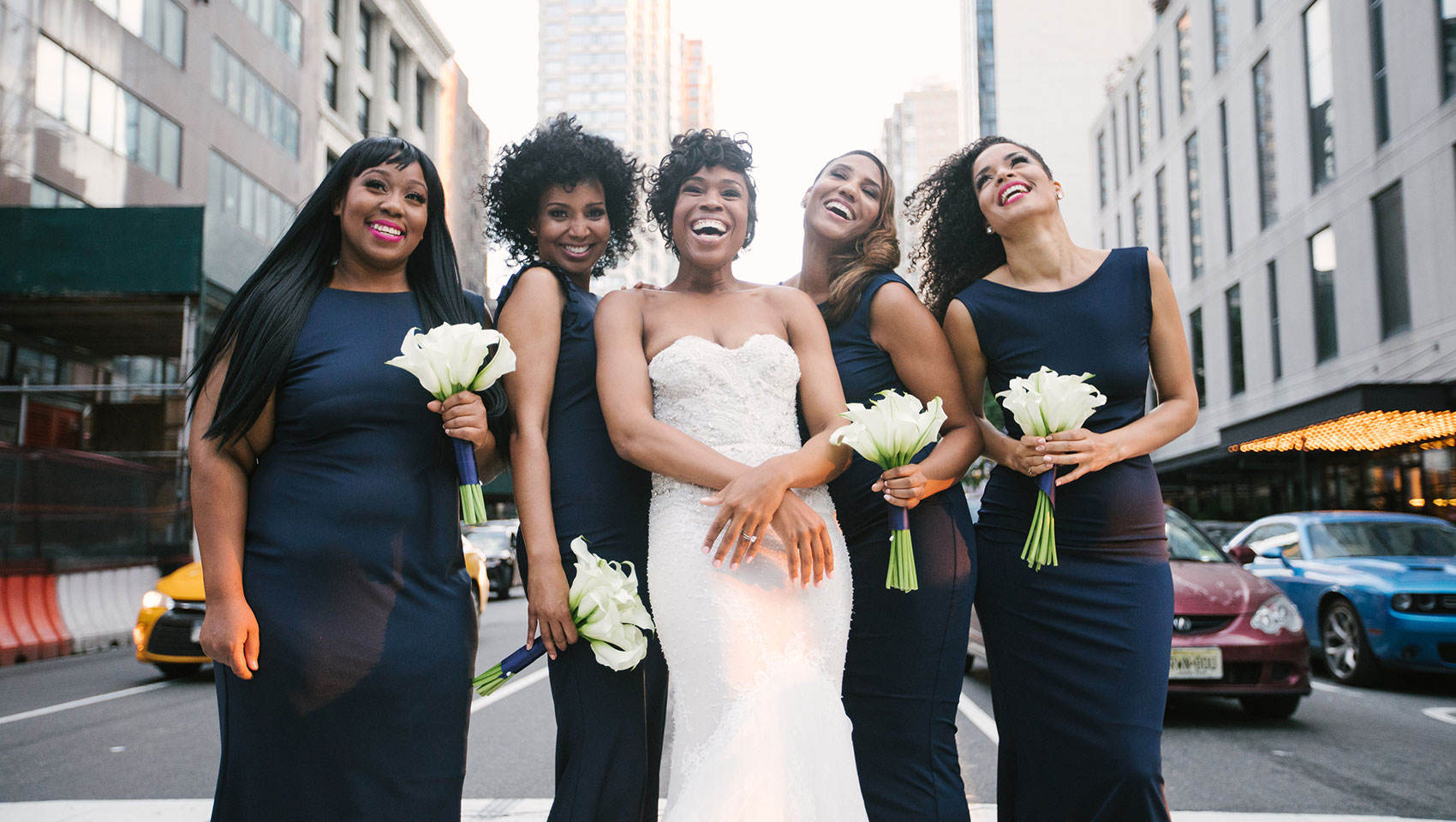 Ahkilah in her wedding dress with bridesmaids holding flowers on a street crosswalk