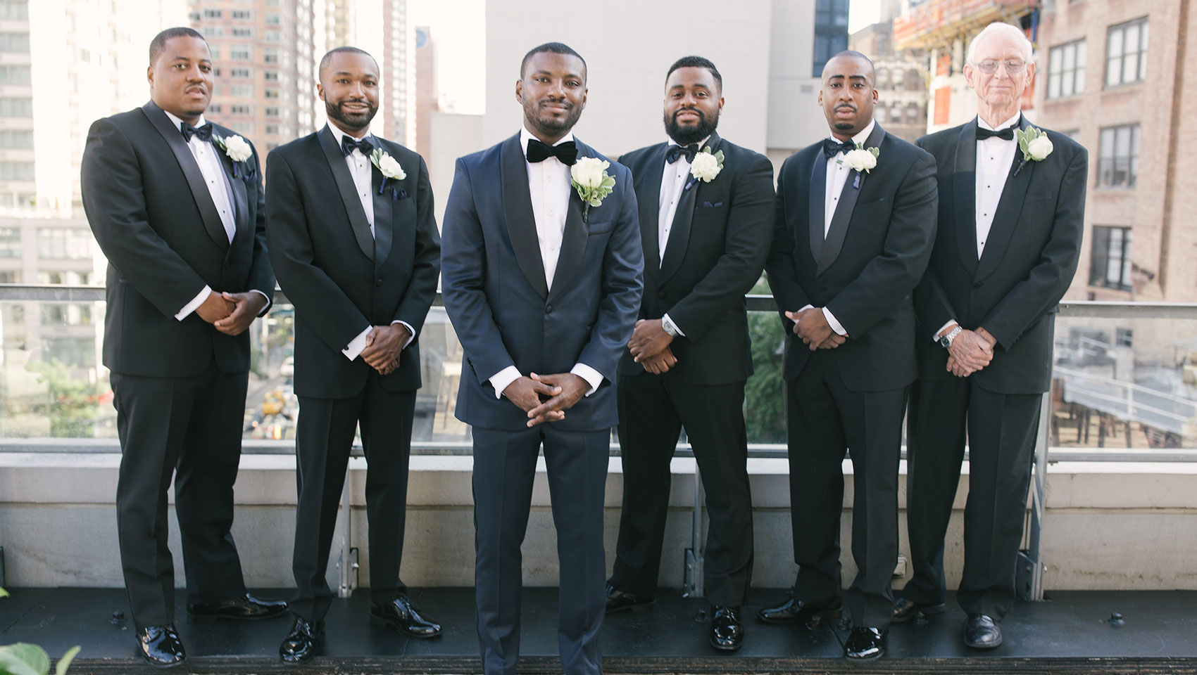 weddingsDaniel with his groomsmen in tuxedos on a balcony