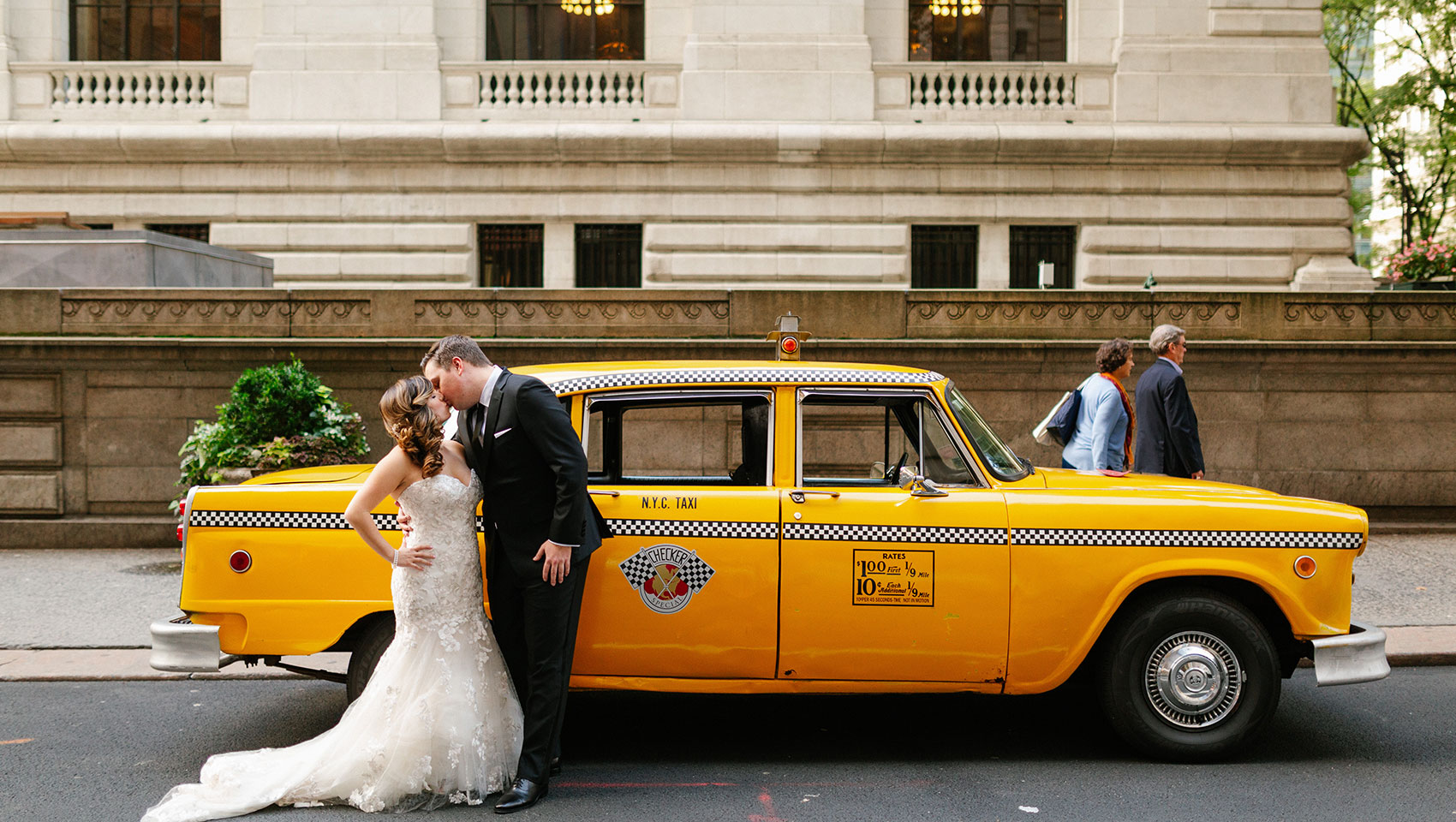 April and Daniel kissing in front of a New York city vintage taxi cab