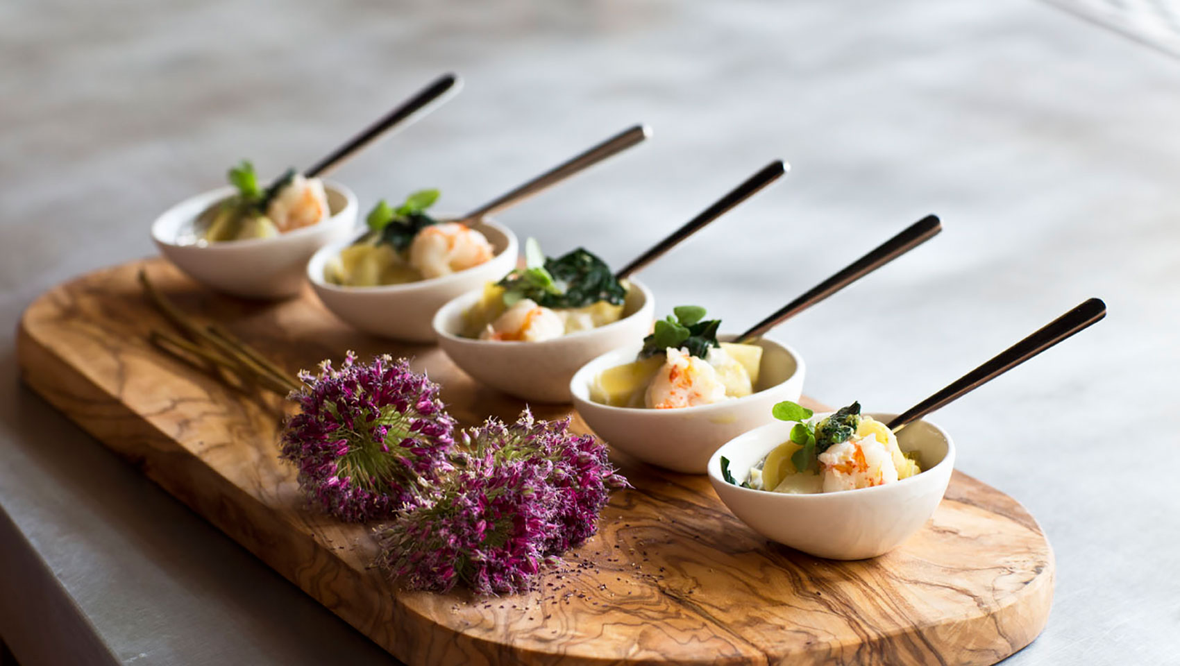 Mini bowls with catering fare placed upon wooden slab