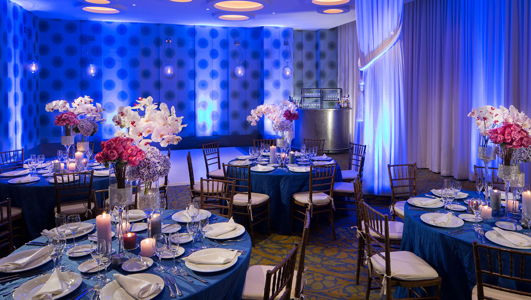 Venue space set up for event with round tables, tall floral arrangements, and dance floor