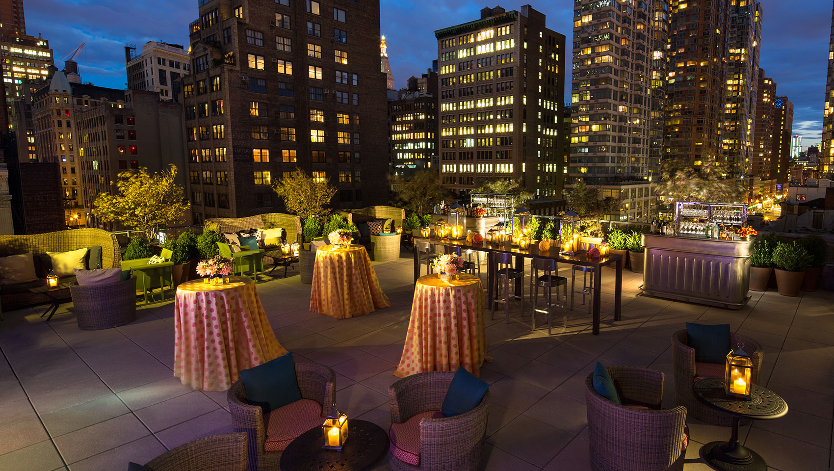 Kimpton Hotel Eventi Veranda set up for outdoor event with tables and bar against city building views at night