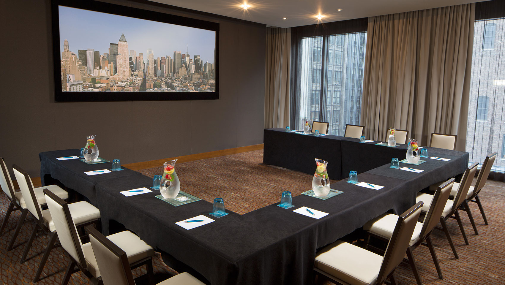 Screening room meeting with u-shape table set up facing towards large presenter screen
