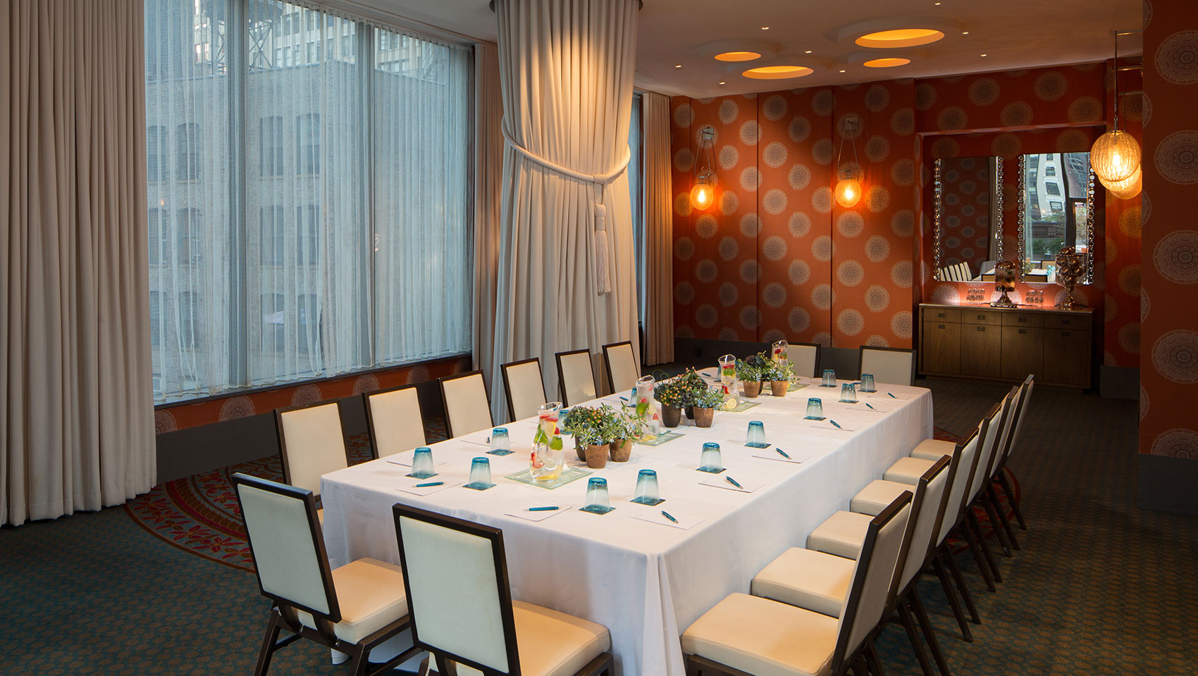 Verdi I boardroom meeting with drawn curtains and meeting table with notepads, floral pieces, and glasses on table