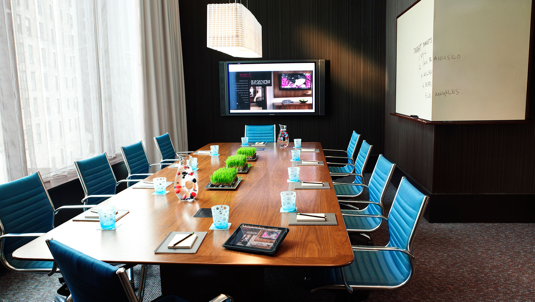 Venture Boardroom with large wooden table with notepads facing presenter screen and wrap-around whiteboard
