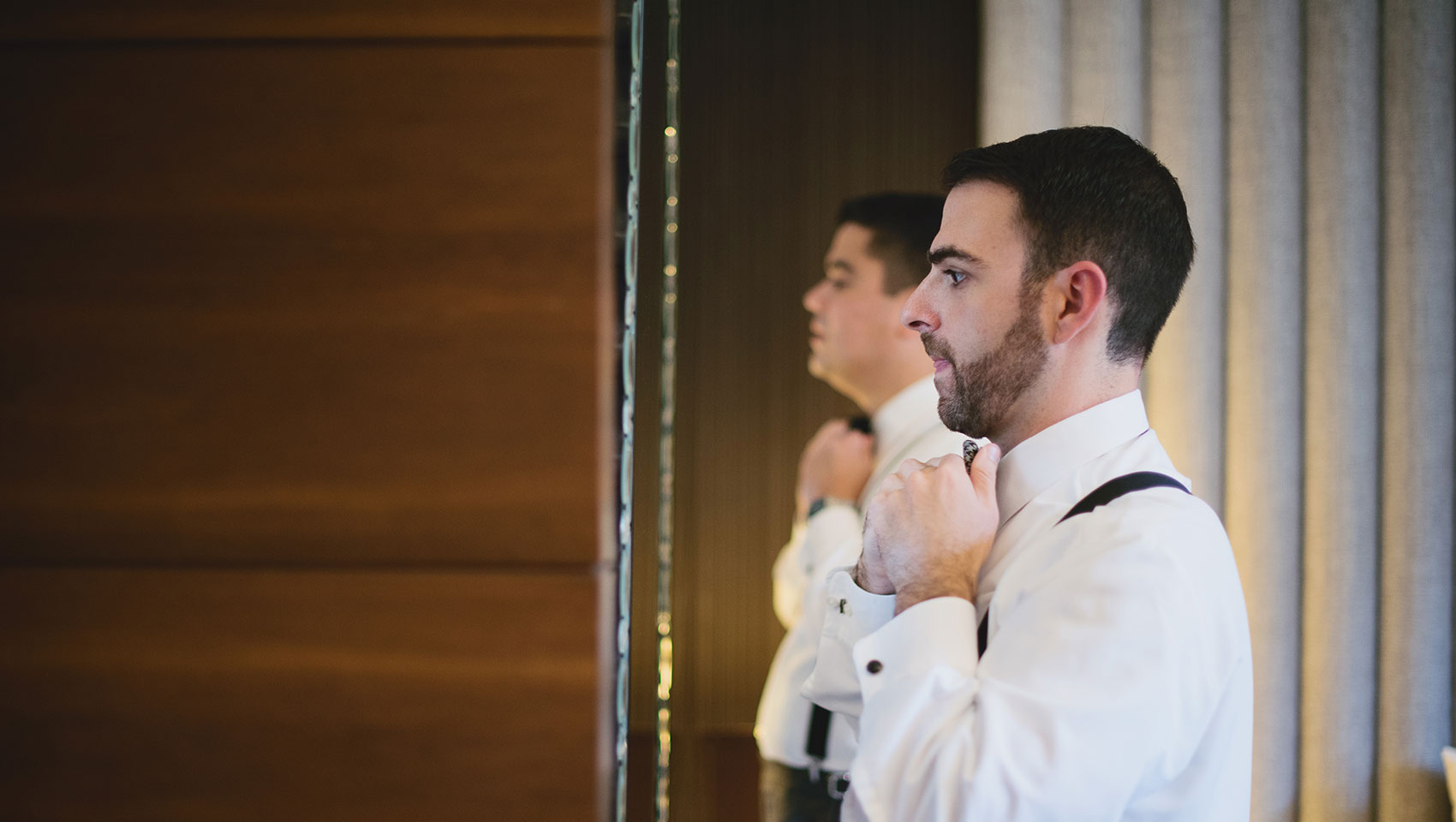 Groom adjusting his bowtie in the mirror on his wedding day