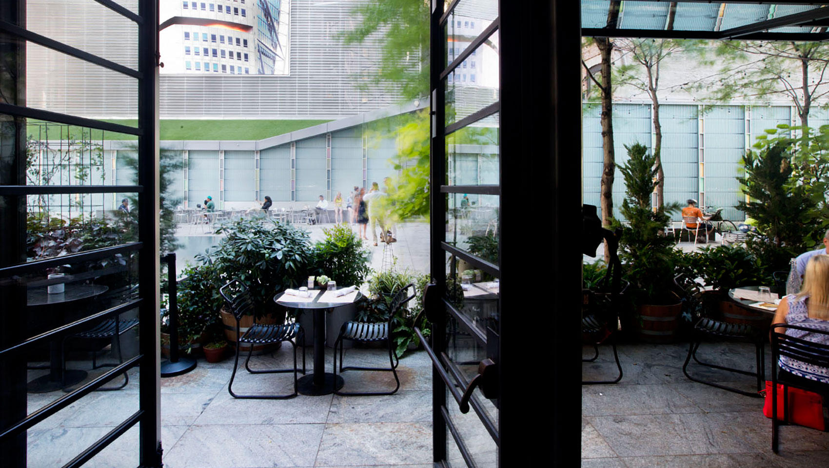 Big screen plaza at Kimpton Hotel Eventi seen through large open windows with plaza greenery and seating