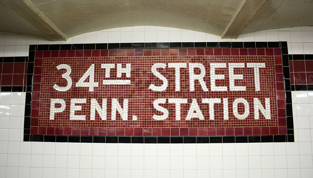 "Tiled wall with tiles that spell out ""34th STREET PENN. STATION"""