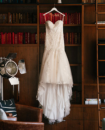 Wedding dress being hung from bookcase