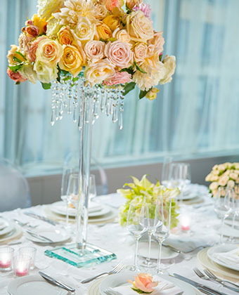 Wedding table setting with plates, candles, and a tall floral centerpiece with draping crystals