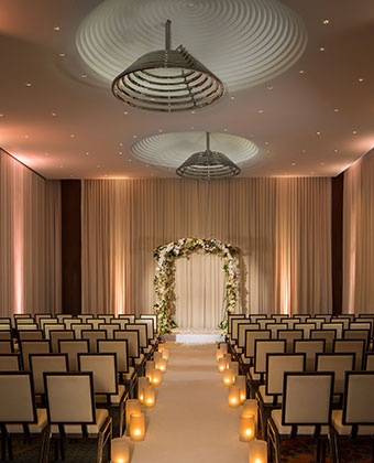 Ventana I wedding set up with chairs facing altar in room with curtains and high ceilings