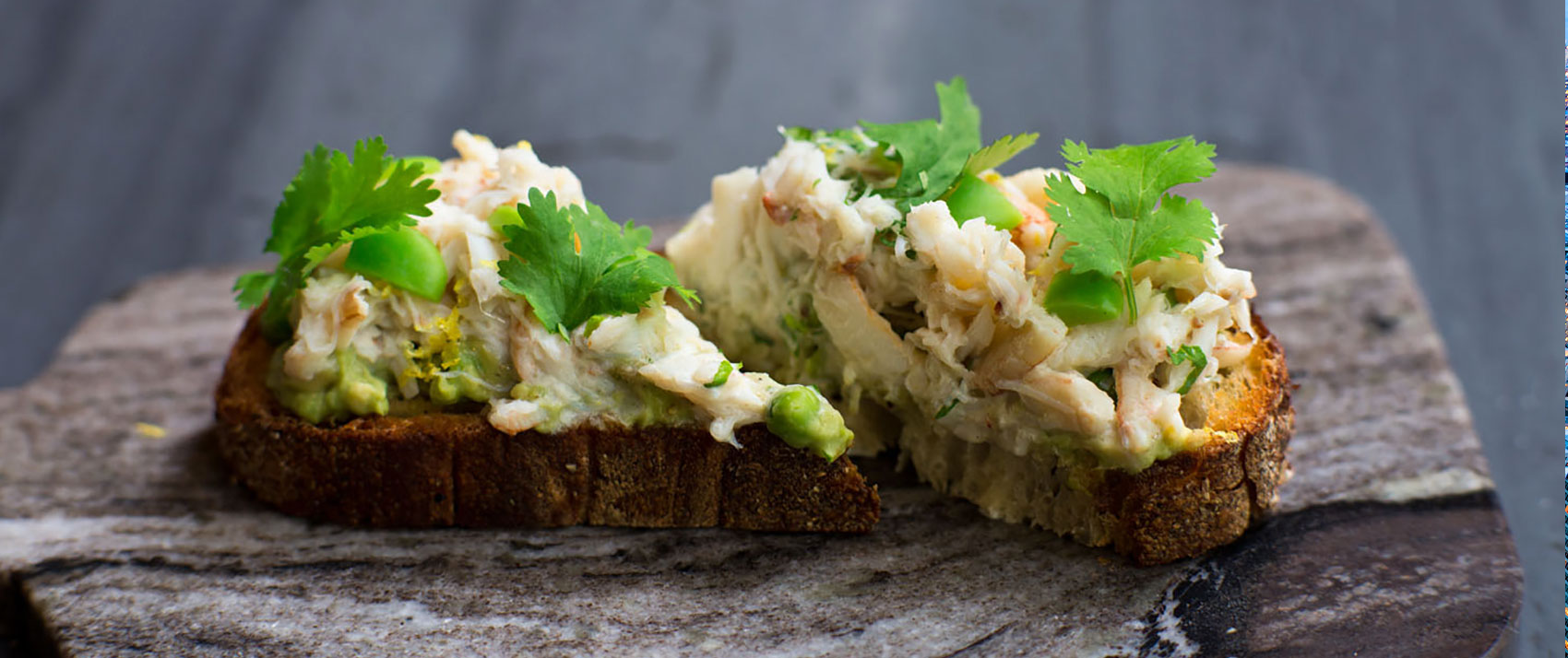 Toast with avocado, herbs, and seafood on top